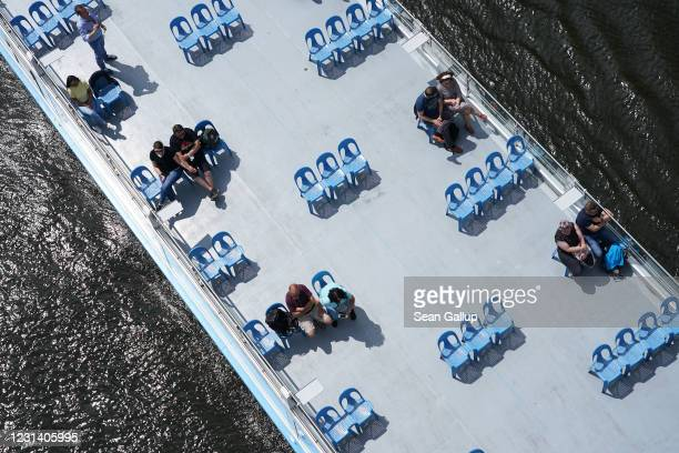 People sit on socially distanced chairs on a sparsely occupied tourist boat on the Spree River during the coronavirus crisis on May 29 2020 in Berlin...