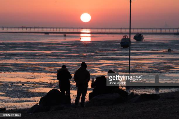 People sit on the beach and watch the sunset over the pier on February 27, 2021 in Southend-on-Sea, England.