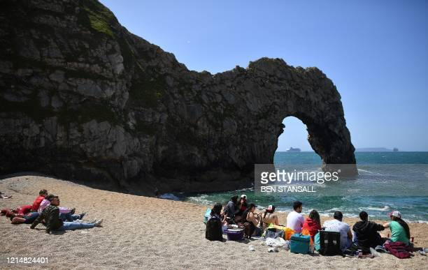 People sit on the beach at the popular tourist spot Durdle Door near West Lulworth on the south coast of England on May 24, 2020. - Travellers...