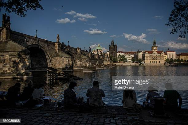 People sit on the bench of Vltava river near the Charles Bridge on May 9 2016 in Prague Czech Republic The Charles Bridge was begun to built in 1357...