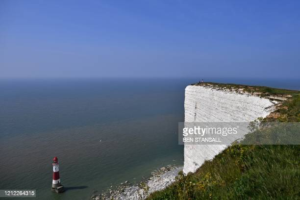 People sit on the cliffs at Beachy Head, near Eastbourne, southern England on May 9 as life in Britain continues over the May bank holiday weekend,...