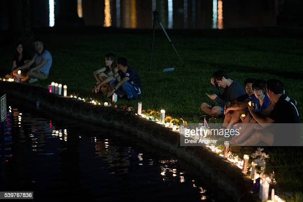 People sit on the edge of Lake Eola where candles were placed for the victims of the nightclub shooting June 12 2016 in Orlando Florida The shooting...