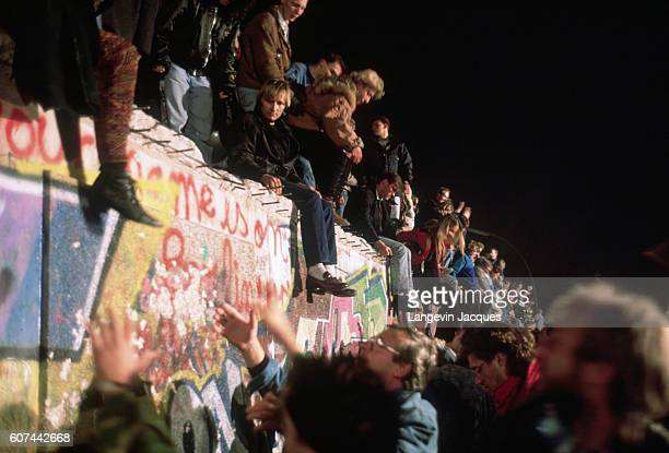People sit on the edge of the Wall as others on the other side stretch out their arms in sympathy during the fall of the Berlin wall between the...