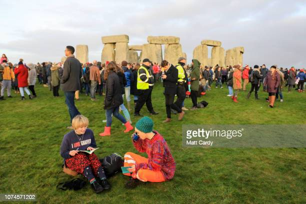 People sit on the grass as druids pagans and revellers gather at Stonehenge hoping to see the sun rise as they take part in a winter solstice...