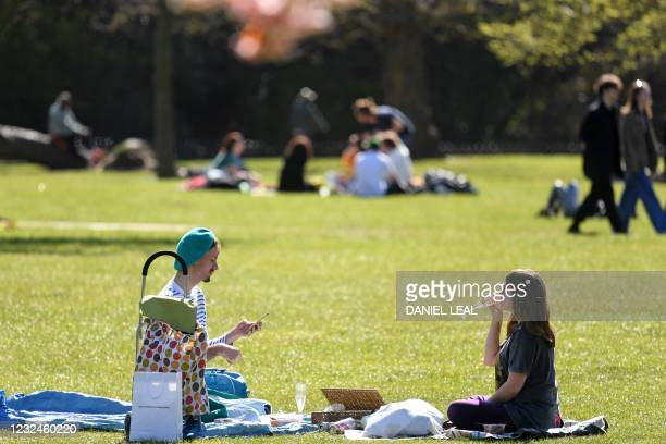 People sit on the grass enjoying the Spring sunshine in Victoria Park, east London on April 22, 2021. - Under the relaxing of the Covid-19 rules,...