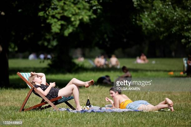 People sit on the grass in the sunshine in Hyde Park in London on June 14, 2021. - Britain was on Monday widely expected to delay the full lifting of...