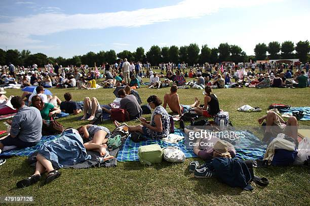 People sit on the grass on day four of the Wimbledon Lawn Tennis Championships at the All England Lawn Tennis and Croquet Club on July 2 2015 in...