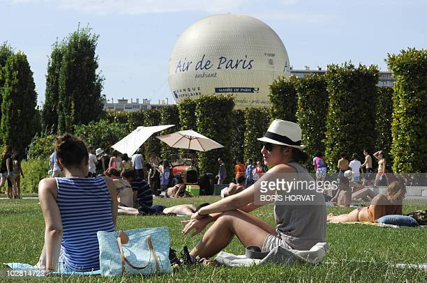 People sit on the grass on July 11 2010 in Paris while enjoying the warm weather at the Parc Andre Citroen in Paris AFP PHOTO BORIS HORVAT