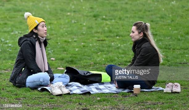 People sit on the grass togather chatting in Battersea Park in London on March 28, 2021. - From Monday, England's stay-at-home order to combat the...