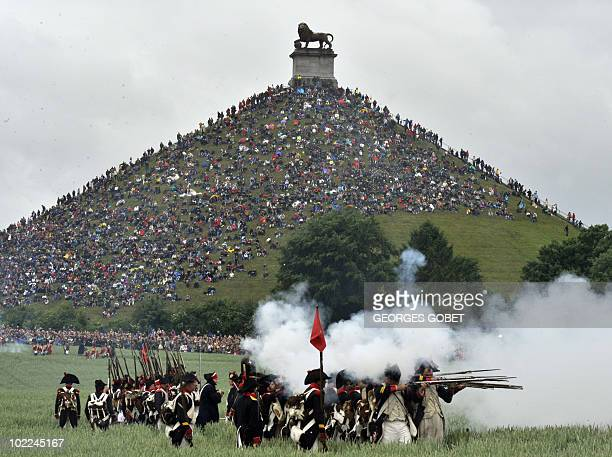 People sit on the Lion's Mound around the lion monument of the Battle of Waterloo during a reenactment of the 1815 Battle of Waterloo between the...