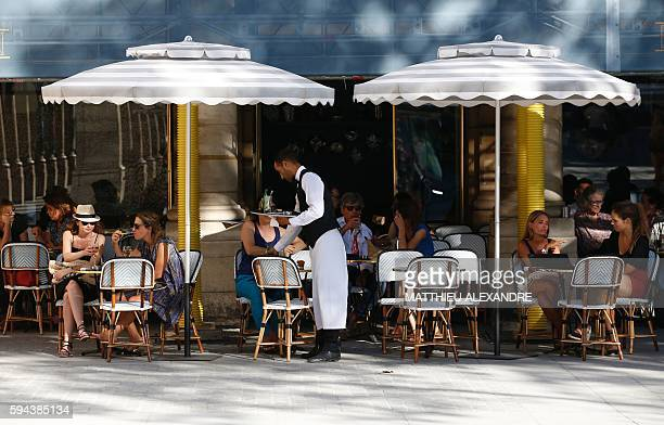 People sit on the outside sitting area of a café by the Jardin du Palais Royal in Paris on August 23 2016 / AFP / MATTHIEU ALEXANDRE
