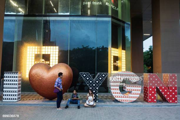 People sit on the pavement outside the Junction City mall in Yangon Myanmar on Friday June 16 2017 A pariah state for decades Myanmars recent...