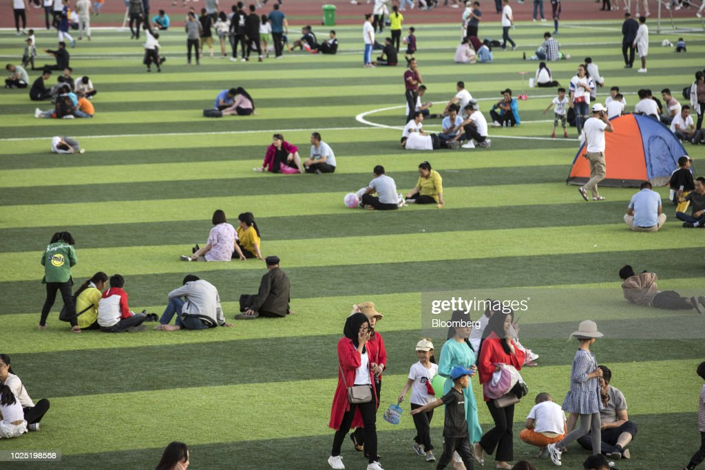 People sit on the pitch at a sports stadium in Golmud, Qinghai province, China, on Sunday, July 22, 2018. Amid rising fears about a trade war, China's policy makers have unveiled measures to boost infrastructure construction and credit to smaller firms, as well as tax cuts. Photographer: Qilai Shen/Bloomberg via Getty Images