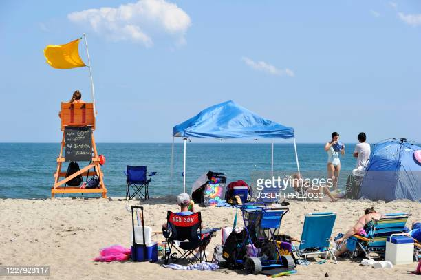 People sit on the sand at Hampton Beach in Hampton New Hampshire on August 5 as COVID19 cases in New England are on the rise Hampton Beach is close...