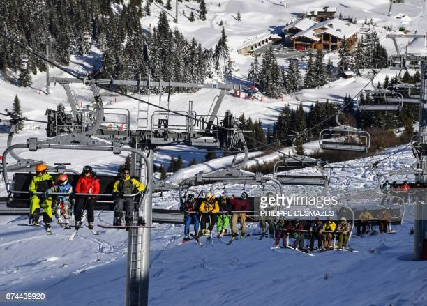 People sit on the ski lifts during an execeptional opening at the ski resort of Courchevel on the French Alps following heavy snowfall on November 15...