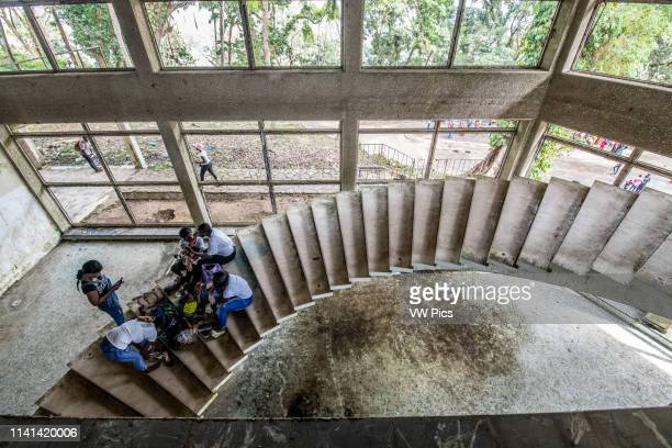 People sit on the stairs of the abandoned Ducor Hotel, once the most prominent hotels in Monrovia, Liberia.