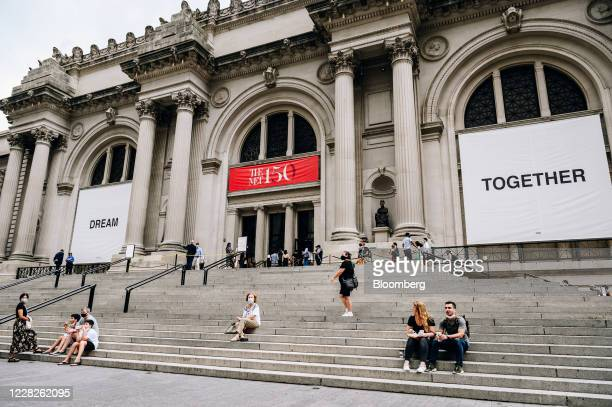 People sit on the steps as visitors wait in line during the public reopening at the Metropolitan Museum of Art in New York, U.S., on Saturday, Aug....