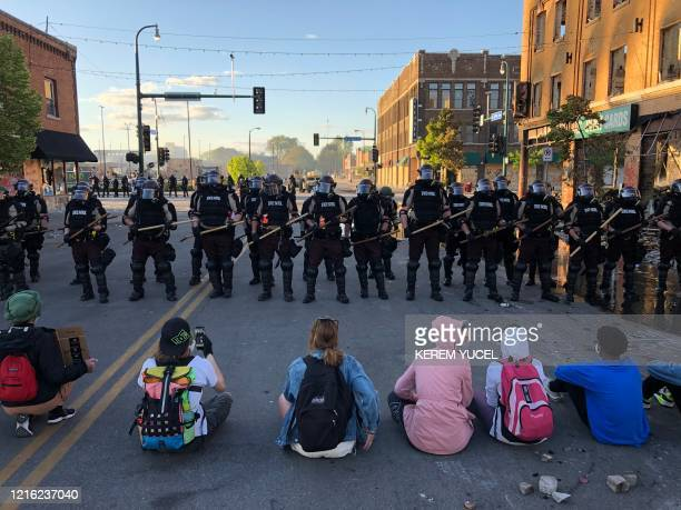TOPSHOT People sit on the street in front of a row of police officers during a rally in Minneapolis Minnesota on May 29 2020 after the death of...