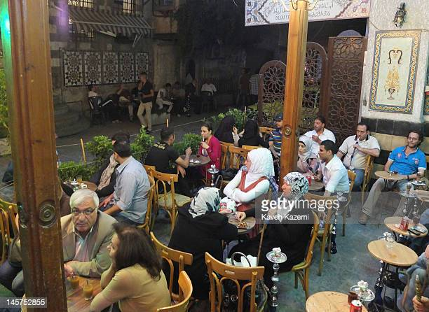 People sit on the terrace of a traditional teahouse smoking waterpipe in Bab Tuma in the old town May 25 2012 in Damascus Syria Despite all the...