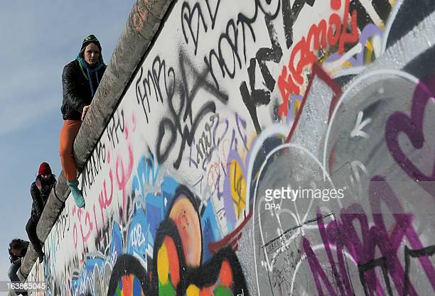 People sit on the Wall to watch US actor and singer David Hasselhoff touring the East Side Gallery part of the remains of the former Wall in Berlin...