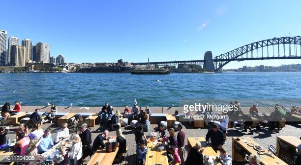 People sit out and eat beside the Harbour Bridge in the afternoon sunshine on August 5 2018 in Sydney Australia Sydney has has 13 days of at least 20...