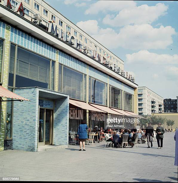 People sit outdoors at cafe tables on Karl Marx Avenue in East Berlin Germany 1967