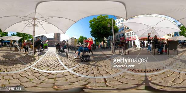 People sit outdoors marked up with a social distance of 1.50 meters minimum to other guests at a cafe the day after restaurants and cafes were...