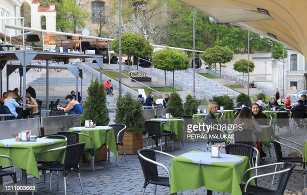 People sit outside a cafe in Vilnius Lithuania on May 5 amidst the new coronavirus COVID19 pandemic The Lithuanian government extended the nationwide...