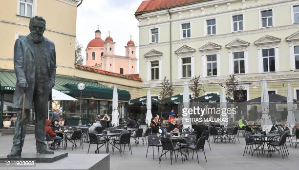 People sit outside a cafe in Vilnius, Lithuania, on May 5 amidst the new coronavirus COVID-19 pandemic. - The Lithuanian government extended the...