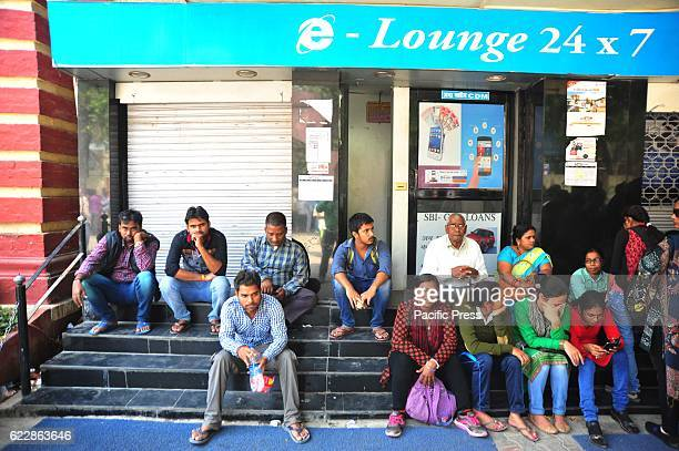 People sit outside a closed ATM in Allahabad