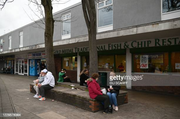 People sit outside a Fish & Chip restaurant in Ashton-under-Lyne east of Manchester in north-west England on November 11 as people in England live...
