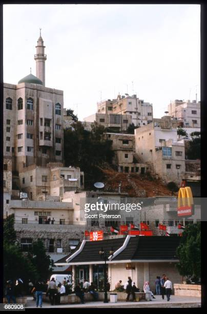 People sit outside a McDonald's restaurant May 17 1998 in Amman Jordan Still a teenager when crowned in 1952 King Hussein has led the young Arab...