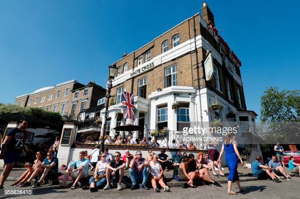 People sit outside a pub on the banks of the River Thames as they soak up the sun in Richmond south west London on May 7 2018 Temperatures on Monday...