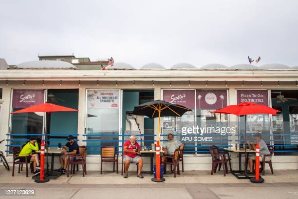 people sit outside a restaurant and bar in Hermosa Beach Los Angeles California on July 14 2020 California's Governor Gavin Newsom announced a...