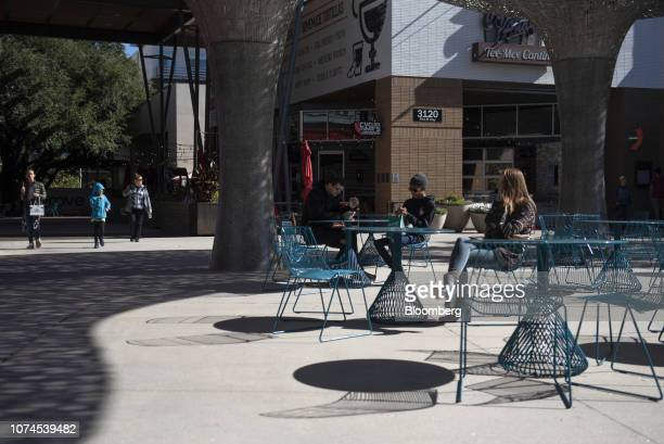 People sit outside a restaurant at the Domain shopping center in Austin Texas US on Thursday Dec 20 2018 Apple Inc announced this month it's opening...