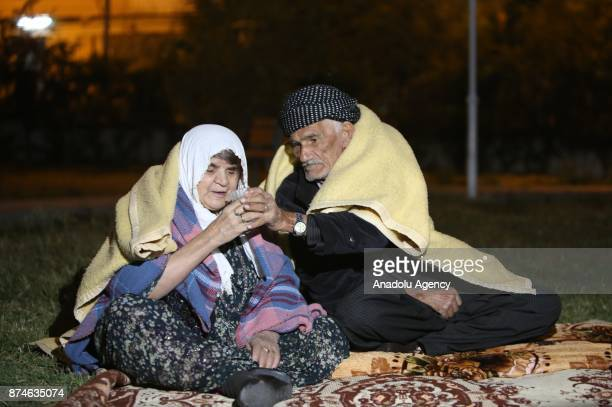 People sit outside as a precaution during night at Darbandikhan district of Suleymaniyah after an earthquake measuring 73 on the Richter scale rocked...