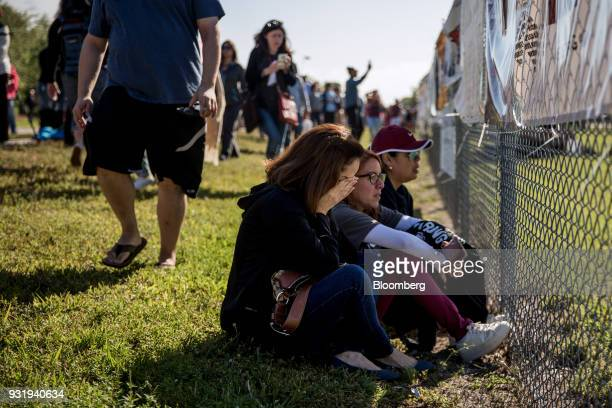 People sit outside as students participate during the ENOUGH National School Walkout rally at Marjory Stoneman Douglas High School in Parkland...