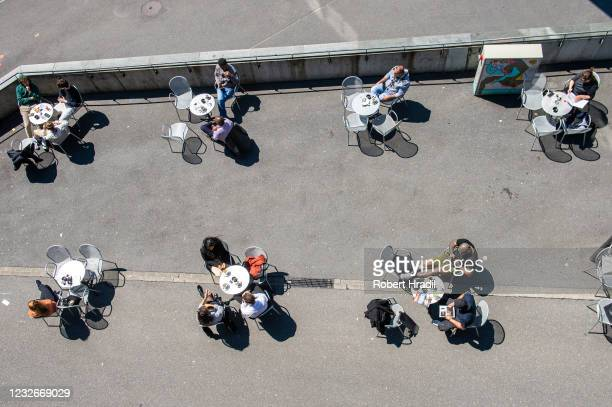 People sit outside at a restaurant during the coronavirus pandemic on May 3, 2021 in Lausanne, Switzerland. Switzerland has eased lockdown...