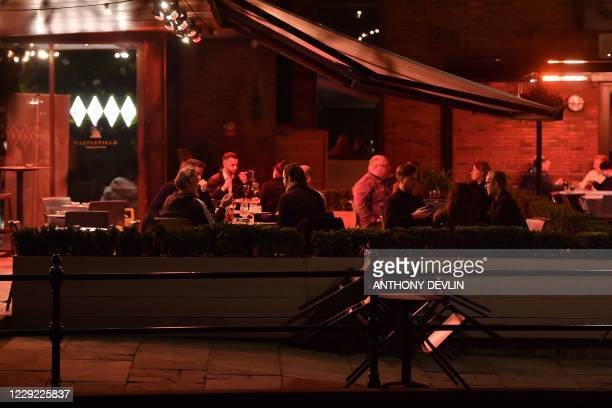 People sit outside Dukes Bar in Castlefield in Manchester city centre northwest England ahead of new coronavirus restrictions coming into force on...