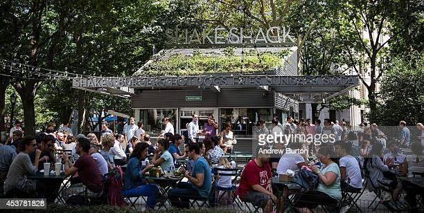 People sit outside Shake Shack on August 18, 2014 in Madison Square Park in New York City. Shake Shack is allegedly considering going public and...