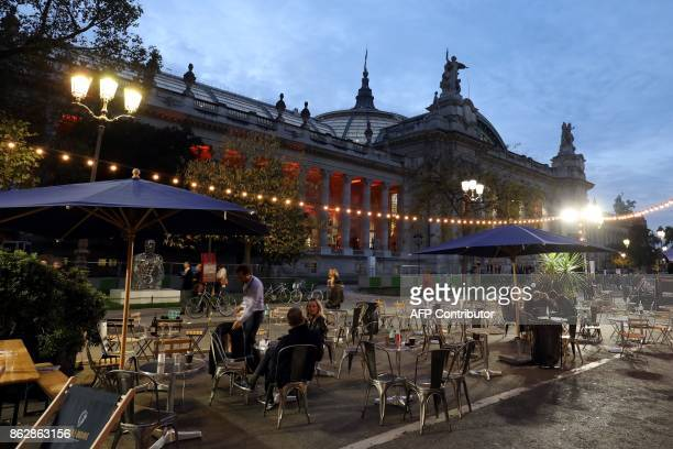 People sit outside the Grand Palais in Paris during the press opening of the Paris International Contemporary Art Fair on Octobre 18 2017 / AFP PHOTO...