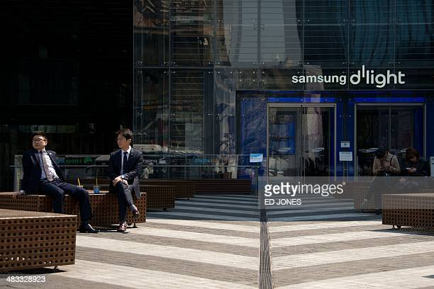 People sit outside the Samsung headquarters in Seoul on April 8 2014 Samsung Electronics posted estimated first quarter operating profits of 84...