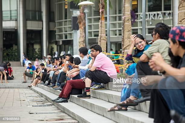 People sit outside the Suria KLCC shopping mall in Kuala Lumpur, Malaysia, on Tuesday, March 18, 2014. Malaysia, aspiring to become a developed...
