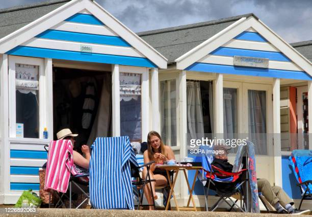 People sit outside their quaint and colourful beach huts at Southwold With the beaches in England now fully opened with only social distancing...