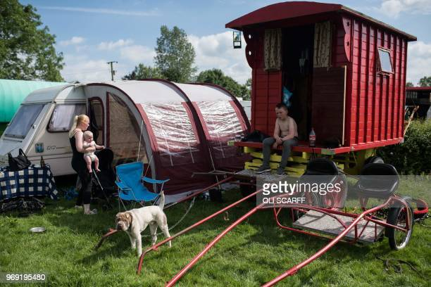 People sit outside traditional gypsy caravans on the opening day of the annual Appleby Horse Fair, in the town of Appleby-in-Westmorland, north-west...