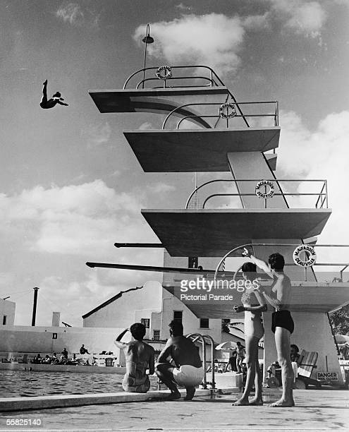People sit poolside and watch as a swimmer dives off the high platform of the Olympicsize swimming pool at the MacFadden Deauville Hotel Miami Beach...