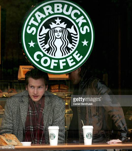 People sit to drink coffee at a Starbucks coffee ctore is seen in central London on April 25, 2006 in London, England. The all traditional English...