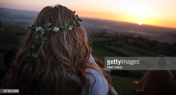People sit to watch the sun rise as they join in a Beltane dawn celebration service in front of St Michael's Tower on Glastonbury Tor on May 1 2013...