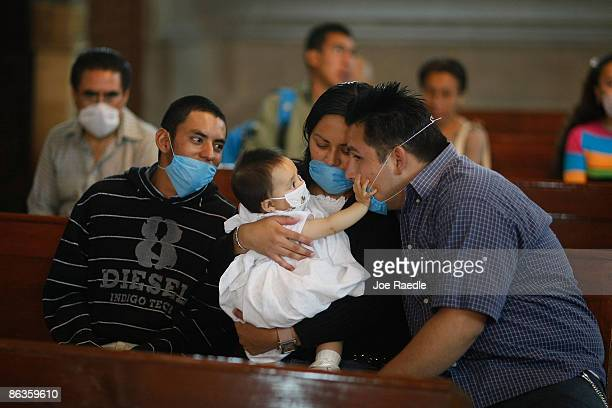 People sit together as they wear surgical masks to help prevent catching the swine flu during a church service on May 3 2009 in Mexico City Mexico...