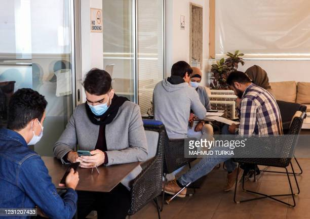 People sit together in a meeting at the Nuqta coworking space, which provides workstations, meeting rooms, and a cafeteria for small businesses and...